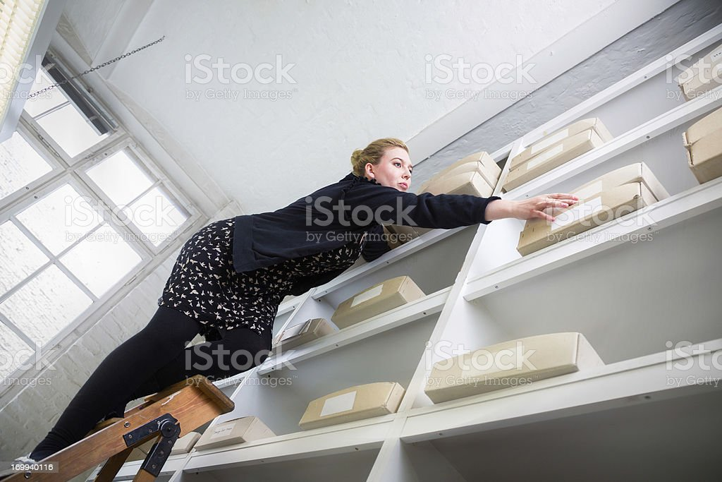 Woman on a ladder reaching for a box out of reach stock photo