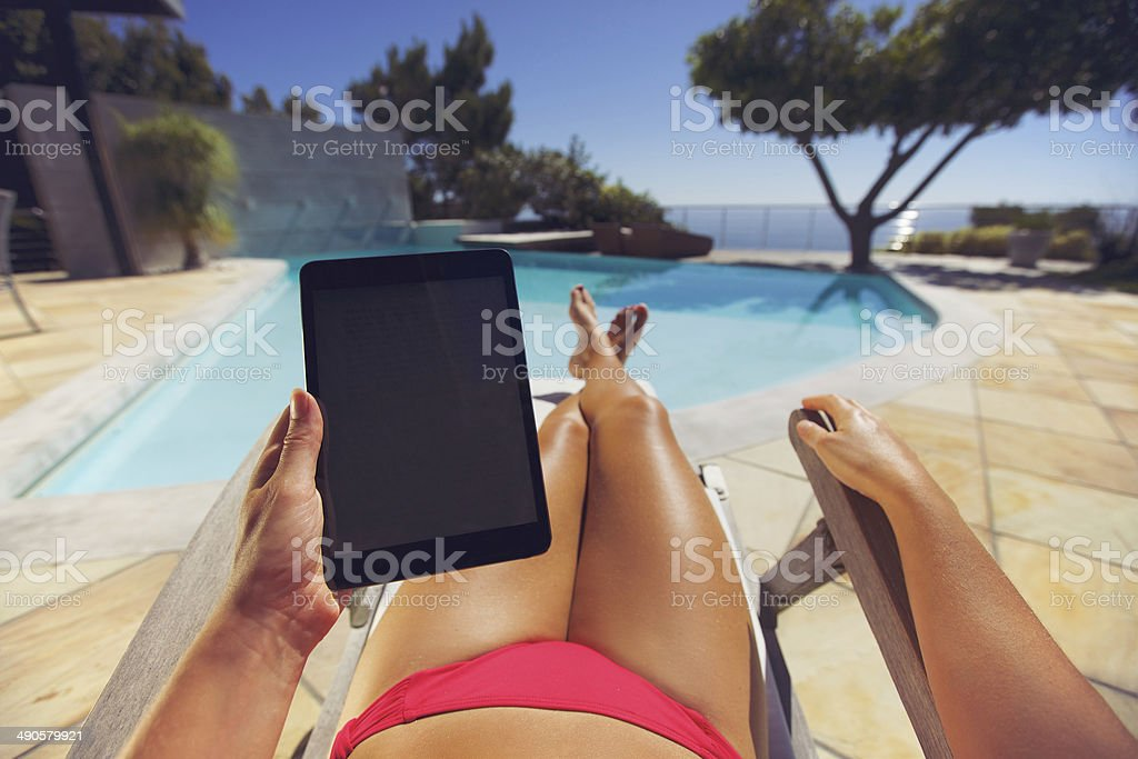 Woman on a lounge chair using tablet PC near pool royalty-free stock photo