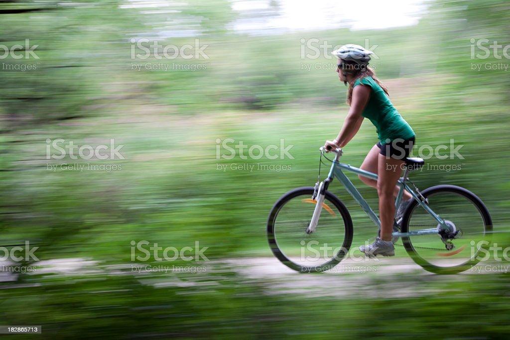 A woman on a mountain bike riding a trail stock photo