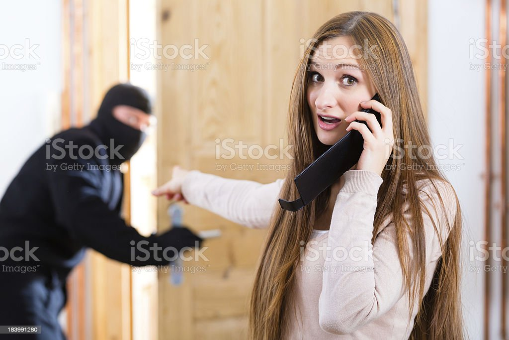 A woman on a phone while pointing at a burglar stock photo