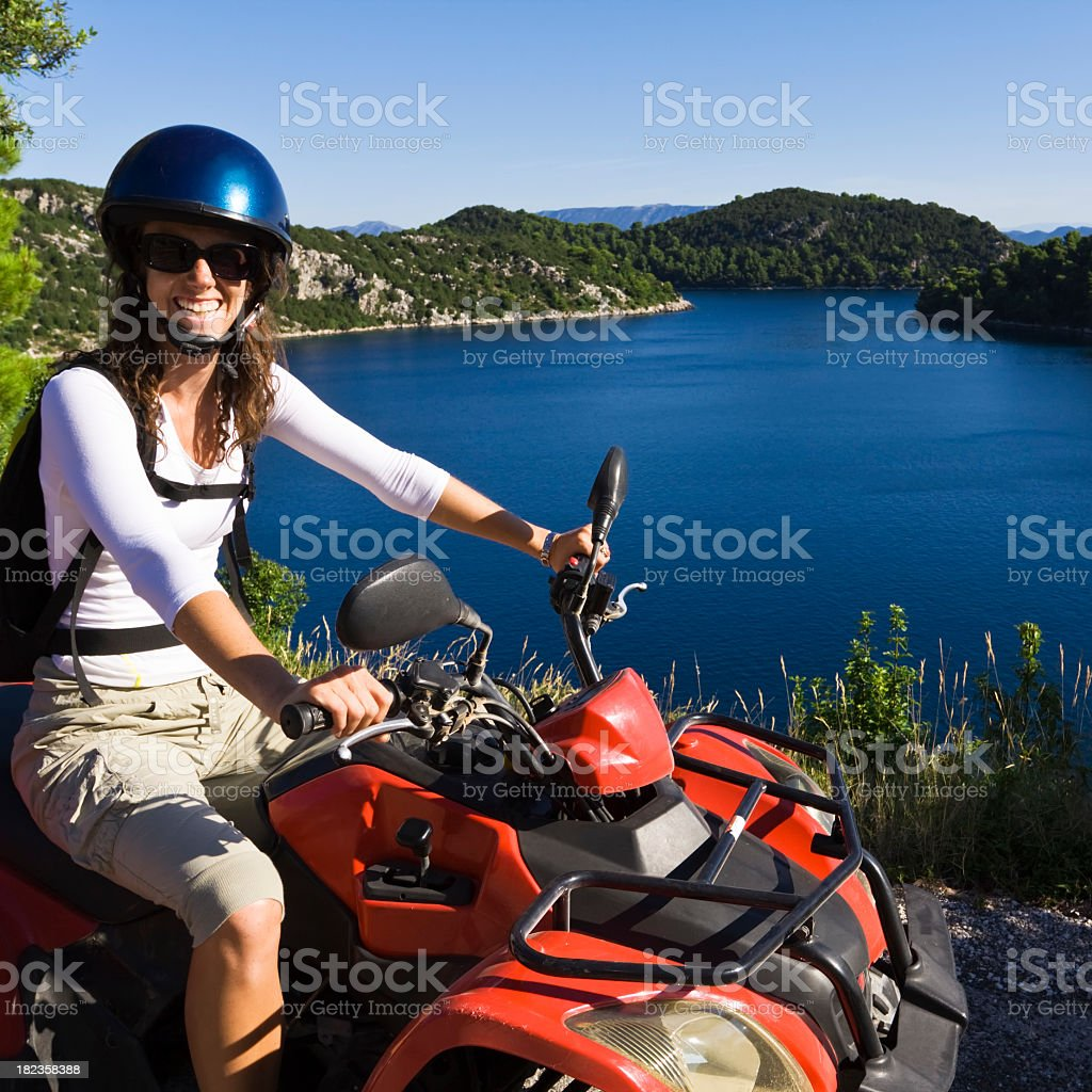 A woman on a red four wheeler sitting in front of blue lake royalty-free stock photo