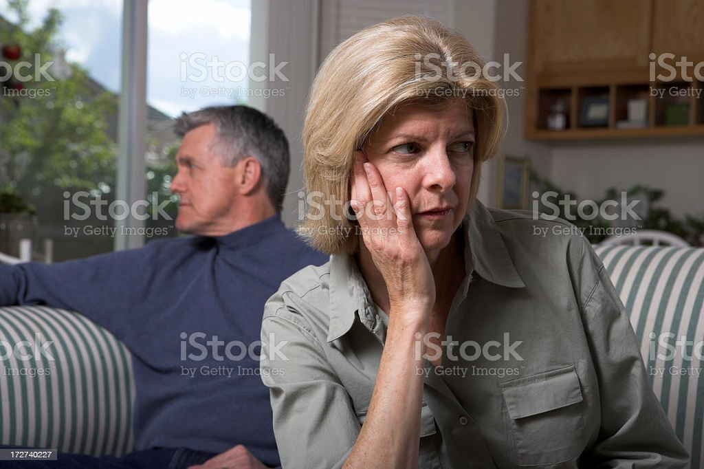 A woman on a sofa looking unhappy with a man sitting behind  royalty-free stock photo