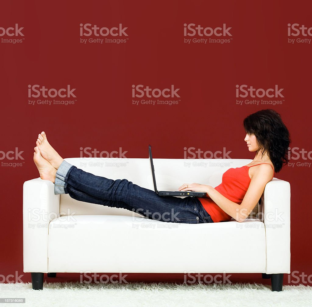 Woman on a sofa with laptop royalty-free stock photo