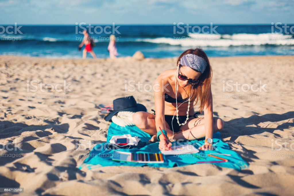 Woman on a summer vacation drawing in coloring book stock photo