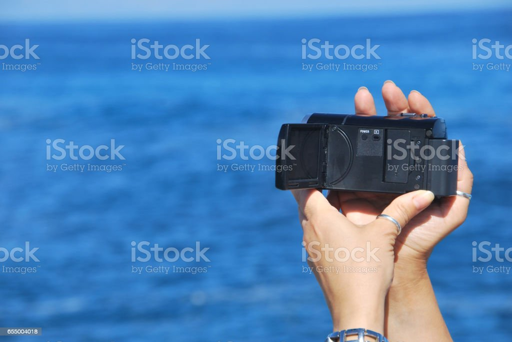 Woman on beach making video stock photo