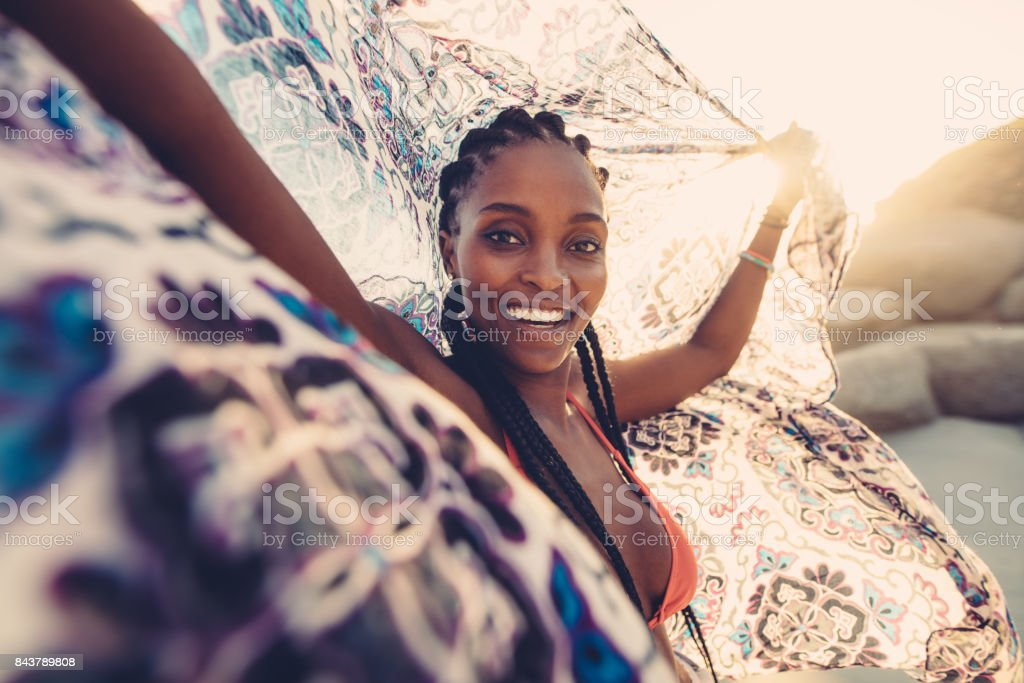Woman on beach with scarf in the breeze stock photo