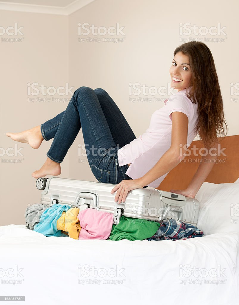 Woman on bed packing her Suitcase (XXXL) royalty-free stock photo