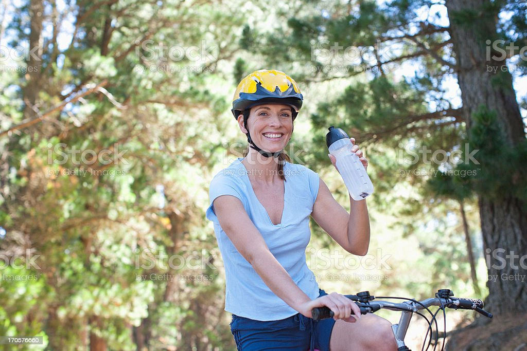 Woman on bicycle drinking water in forest royalty-free stock photo