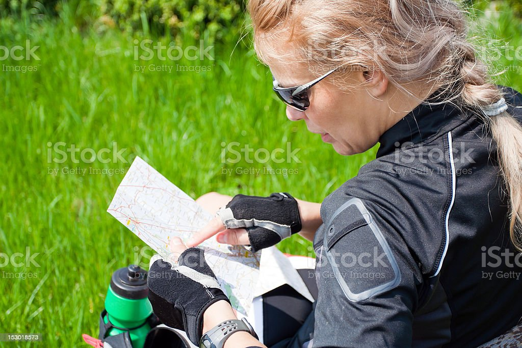 Woman on bicycle trip checking a map royalty-free stock photo
