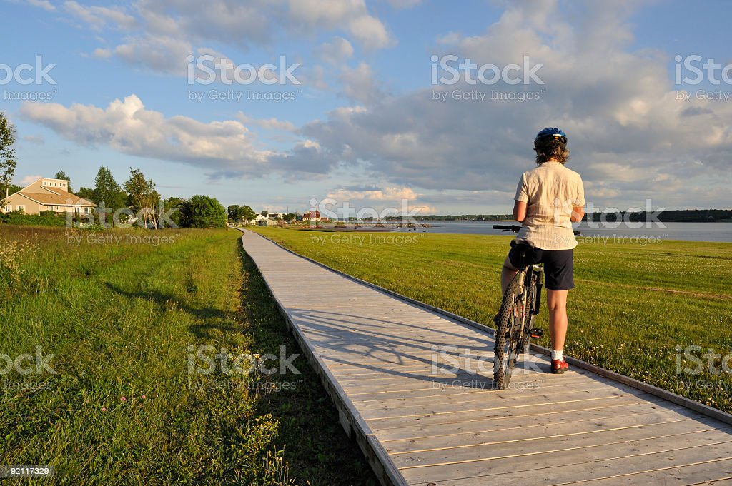 Woman on bike at dusk. royalty-free stock photo