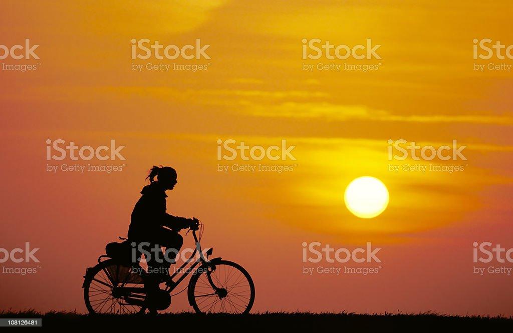 Woman on Bike during Sunrise stock photo