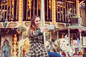 Woman on carousel ride taking selfie