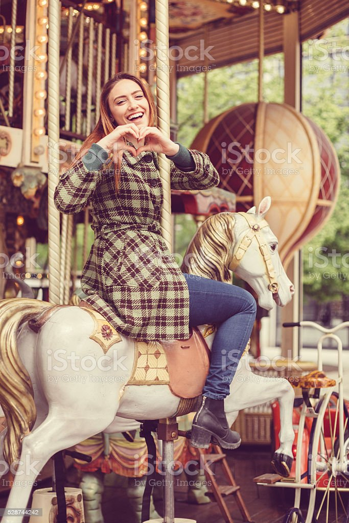Woman on carousel showing love symbol to his boyfriend stock photo