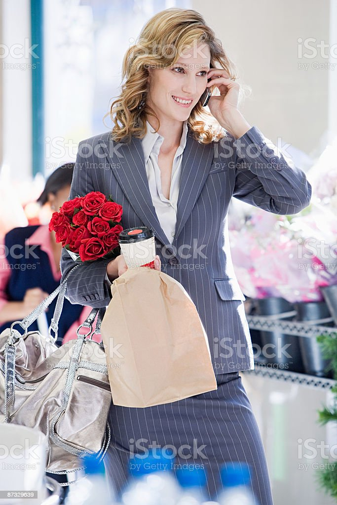 Woman on cellphone in supermarket stock photo