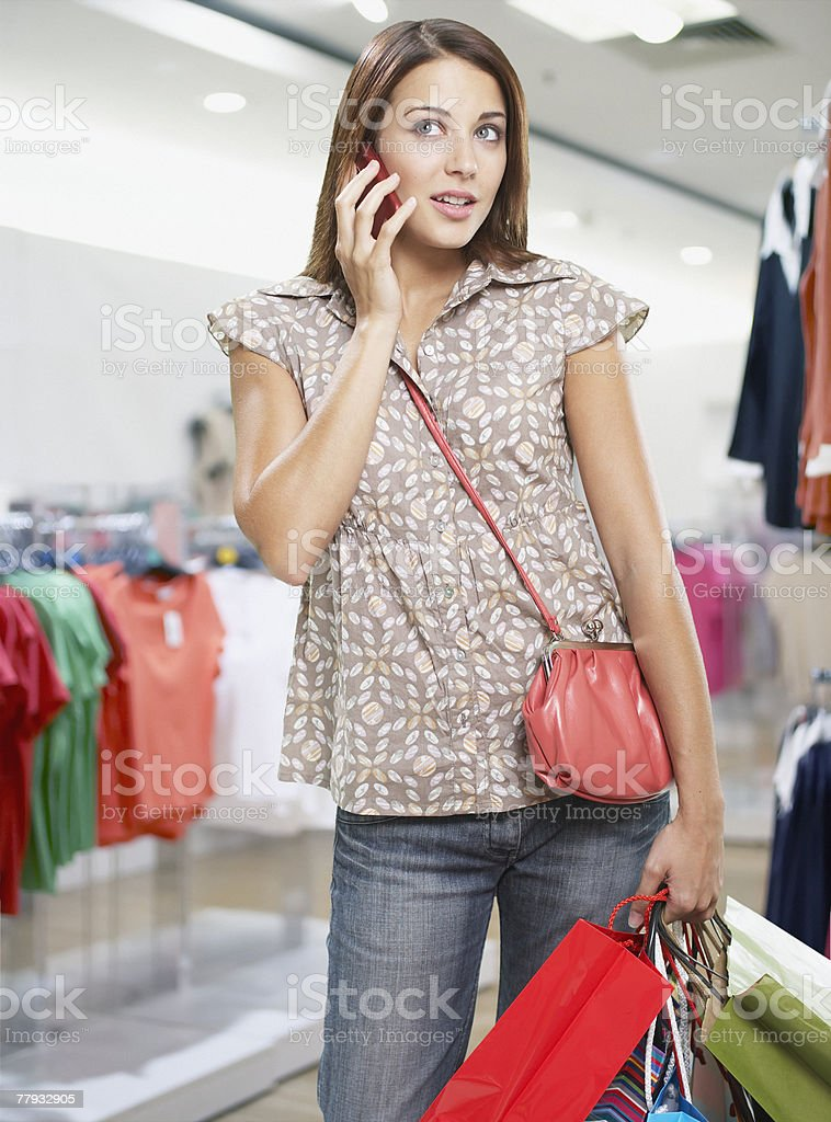 Woman on cellular phone in store royalty-free stock photo