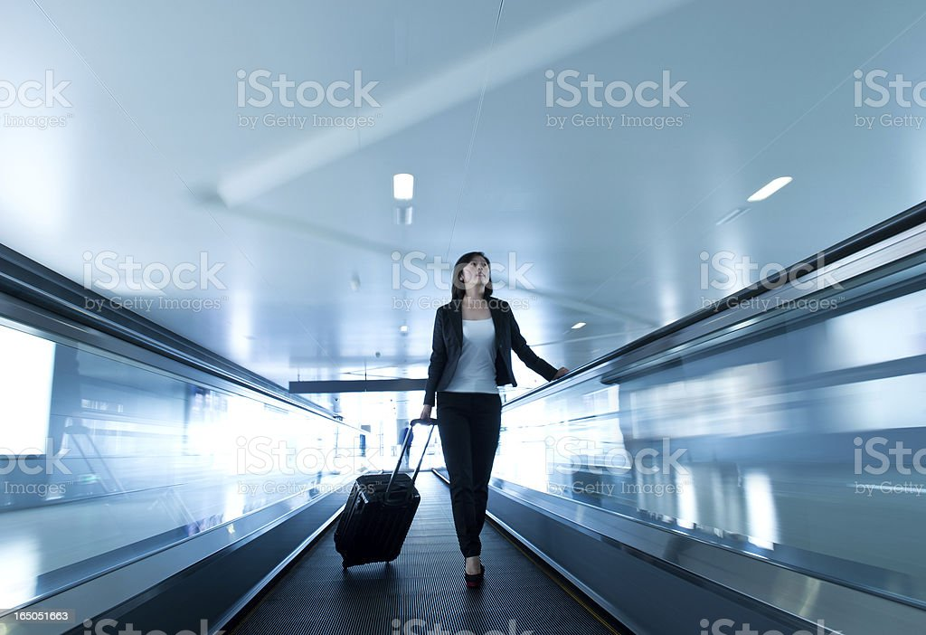 Woman on conveyor pulling trolley suitcase stock photo