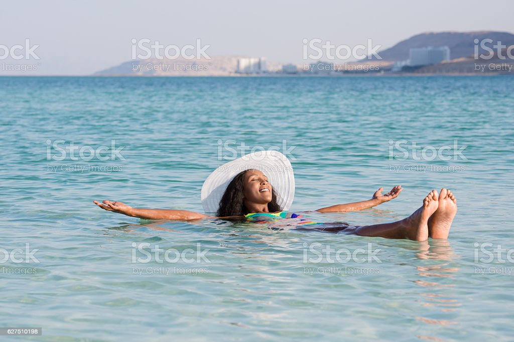 Woman on Dead Sea in perfect vacation. stock photo
