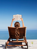 Woman on deck chair reading book