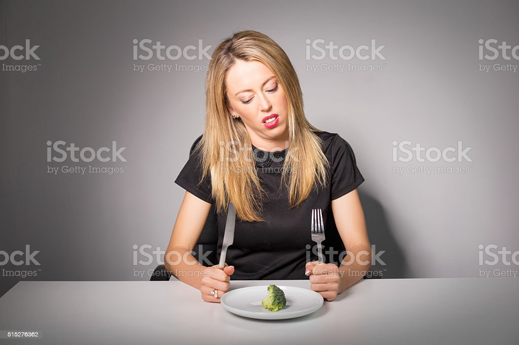 Woman on diet eating broccoli stock photo