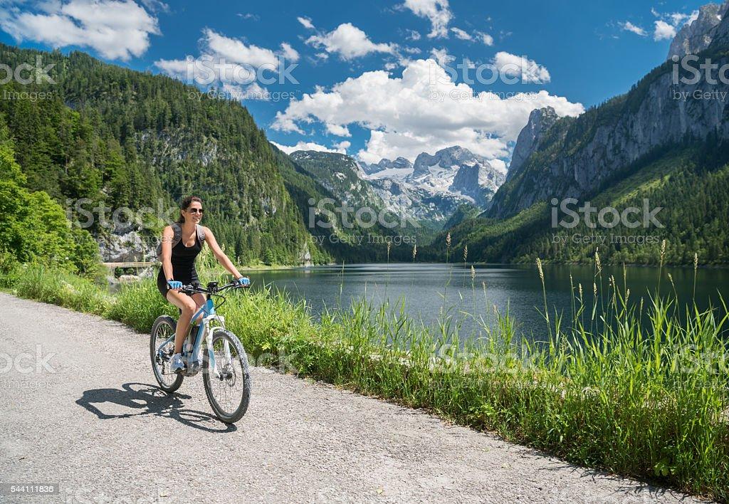 Woman on E-Bike Mountainbike in Nature, Lake Gosau, Dachstein Glacier stock photo
