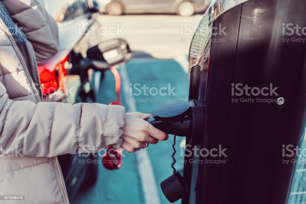 Woman on electric vehicle charging station stock photo