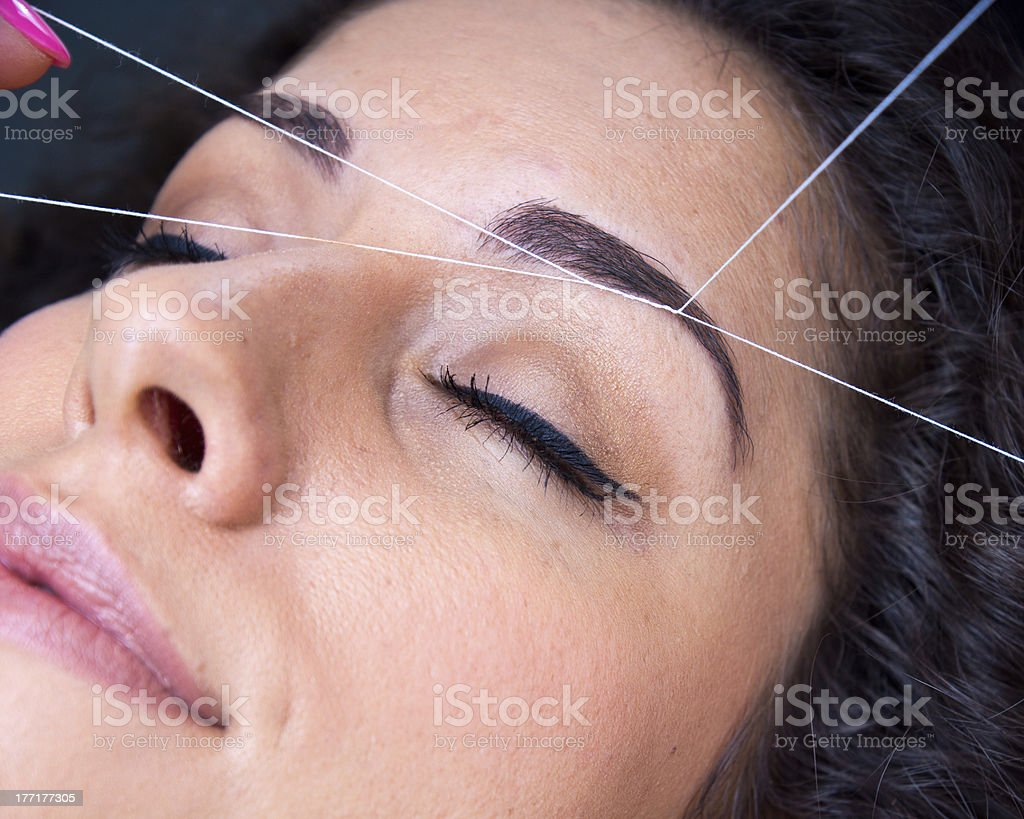 woman on facial hair removal threading procedure stock photo