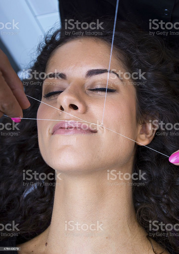 woman on facial hair removal threading procedure royalty-free stock photo