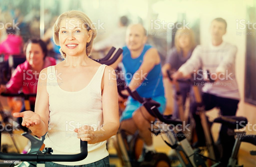 Woman on fitness cycle with people stock photo