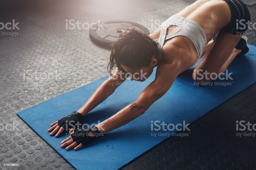 Woman on fitness mat doing stretching workout at gym. stock photo