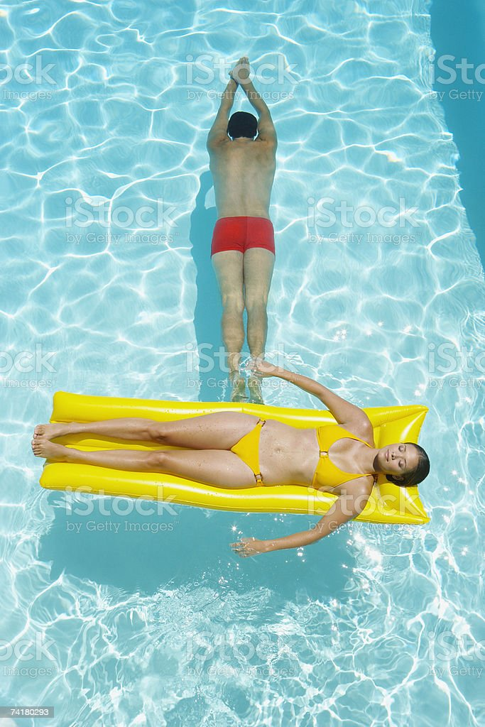 Woman on flotation device and man swimming in pool royalty-free stock photo