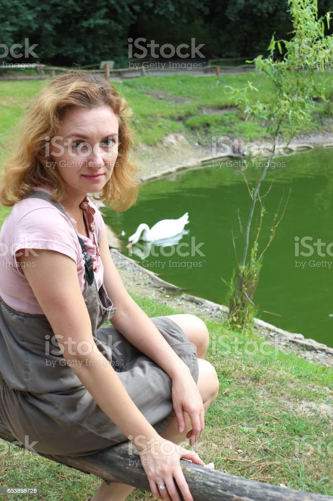 Woman on front of pond with swans. stock photo