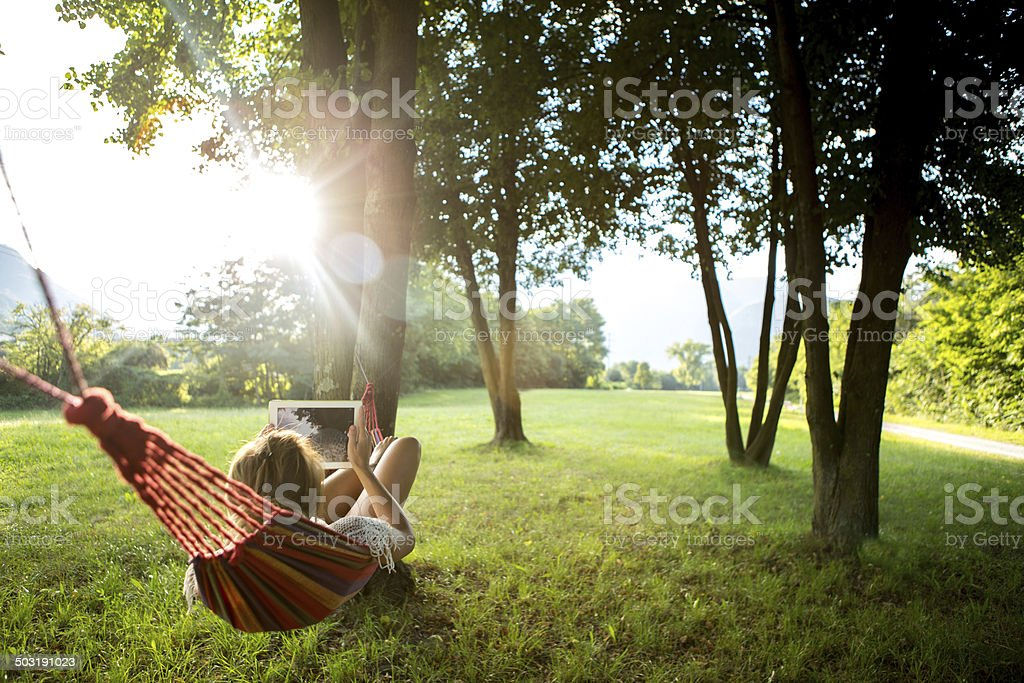 Woman on hammock at sunset taking picture with digital tablet stock photo