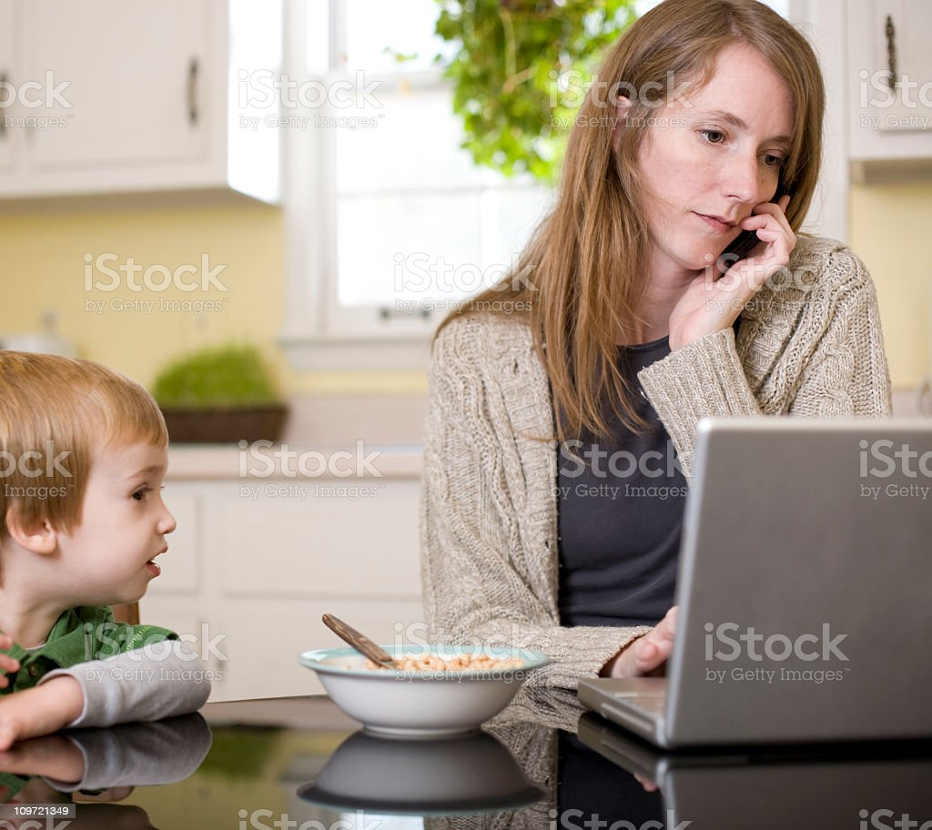 A woman on her mobile and laptop next to a young child royalty-free stock photo