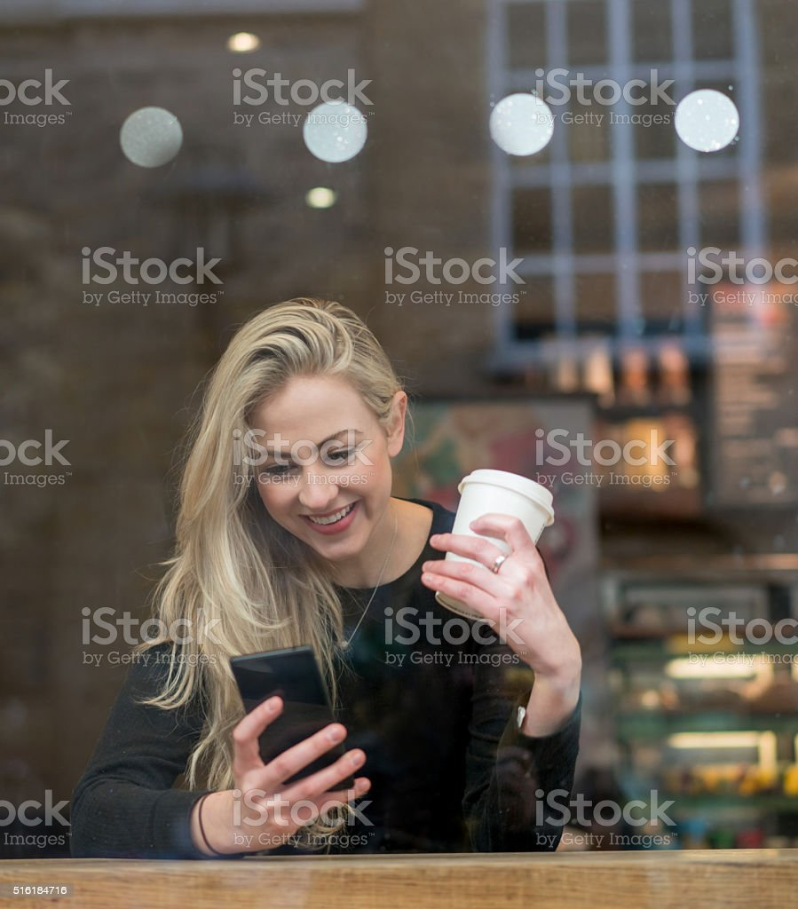 Woman on her phone at a cafe stock photo