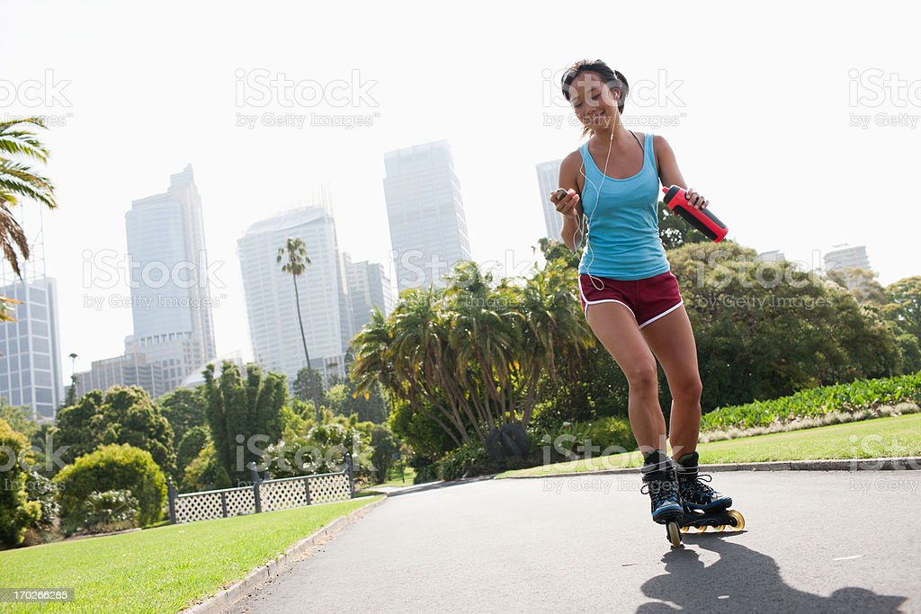 Woman on inline skates looking at mp3 player stock photo