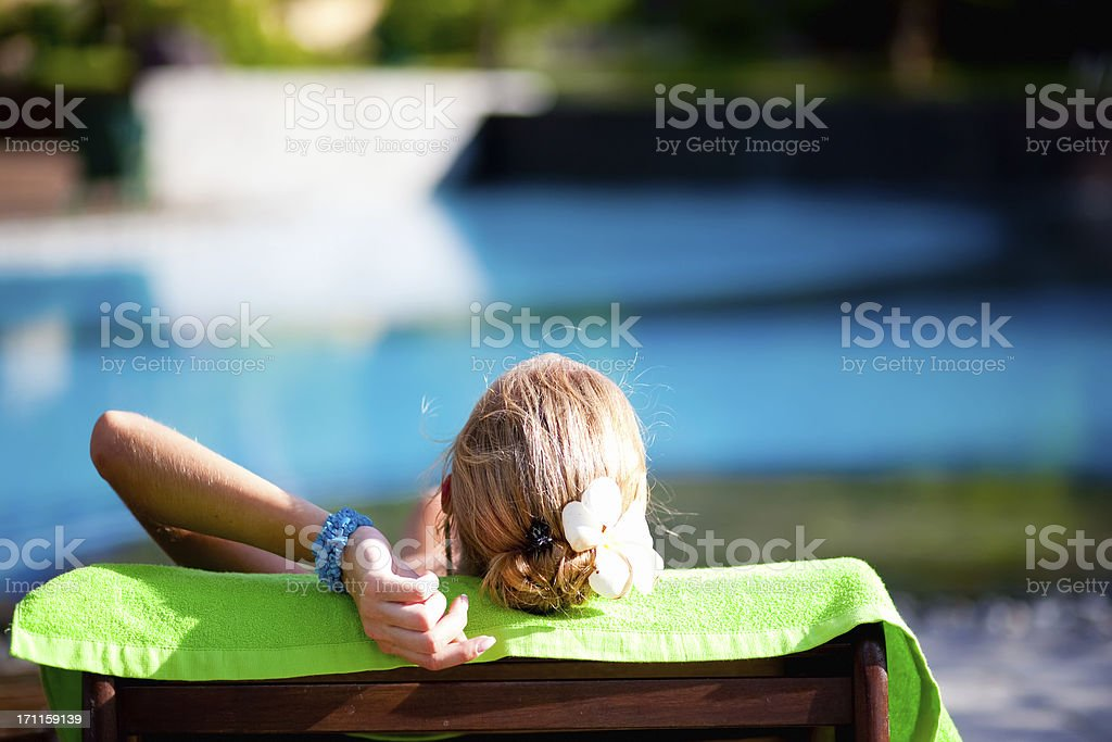 Woman on lawn chair near a swimming pool stock photo