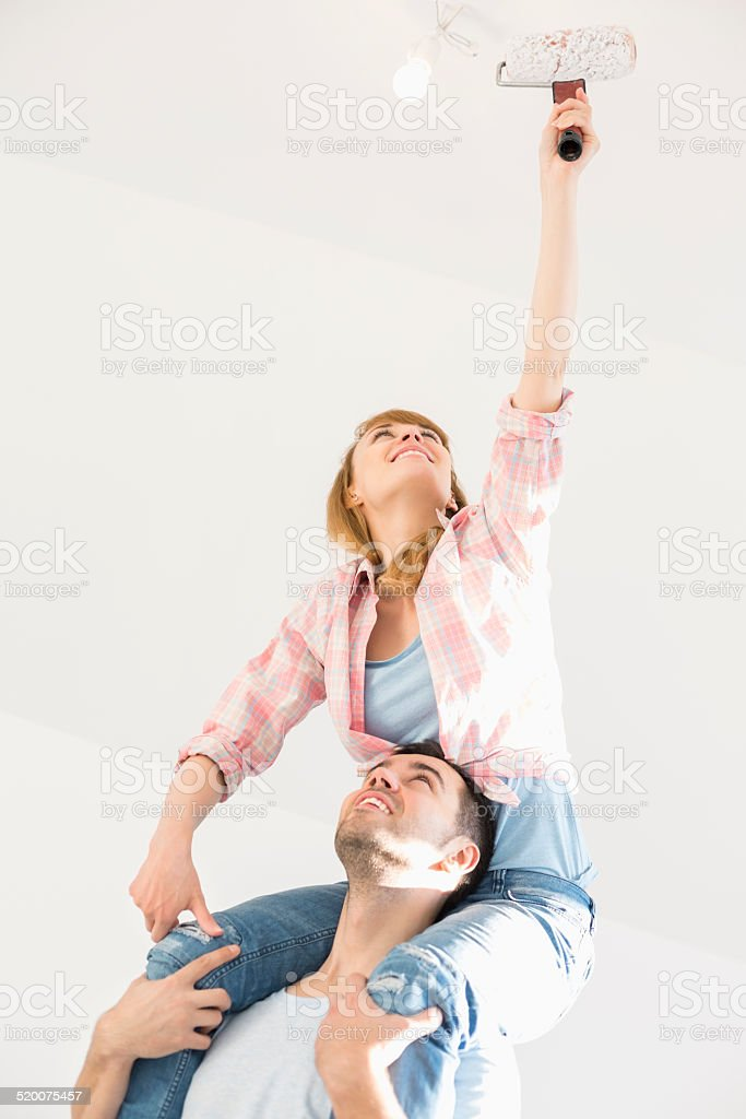 Woman on man's shoulders painting ceiling with paint roller stock photo