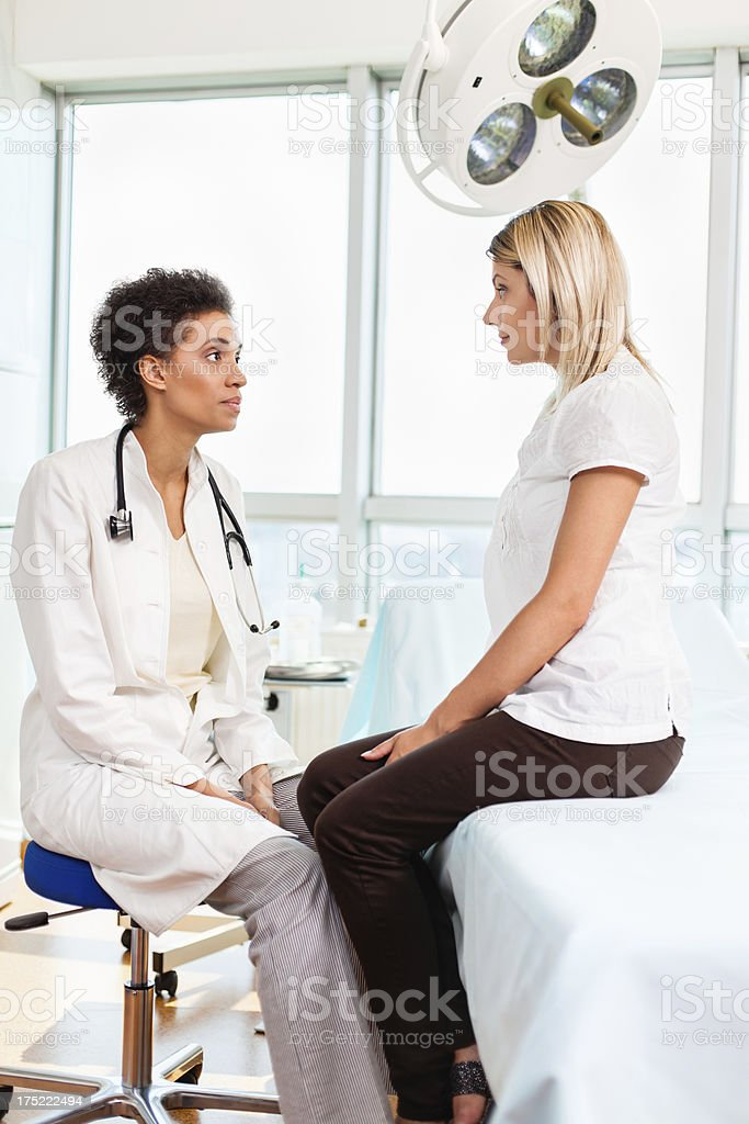 Female doctor talking with patient in doctor\'s office.