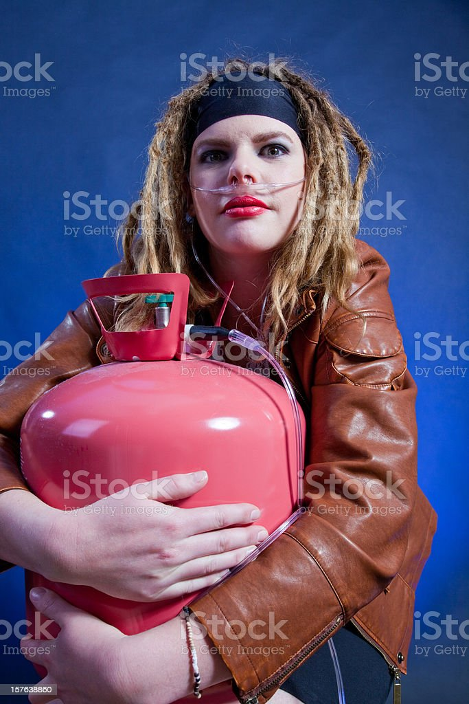 Woman on medical oxygen holding a tank royalty-free stock photo