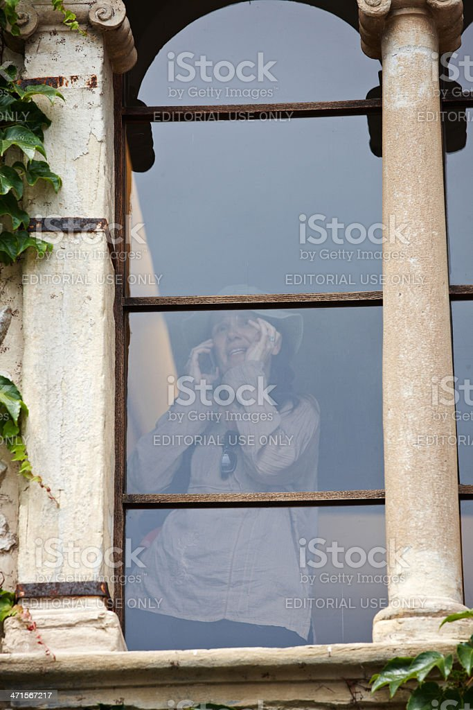 Woman on mobile through old window royalty-free stock photo