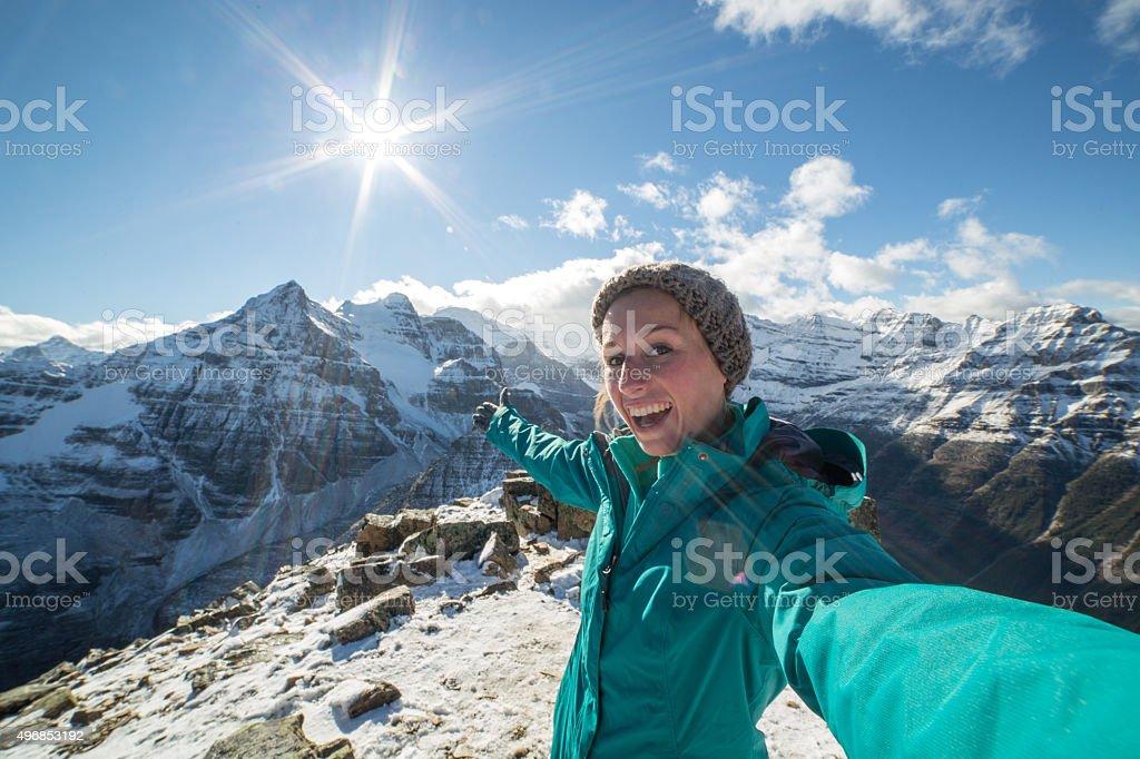 Woman on mountain peak takes selfie portrait with spectacular landscape stock photo