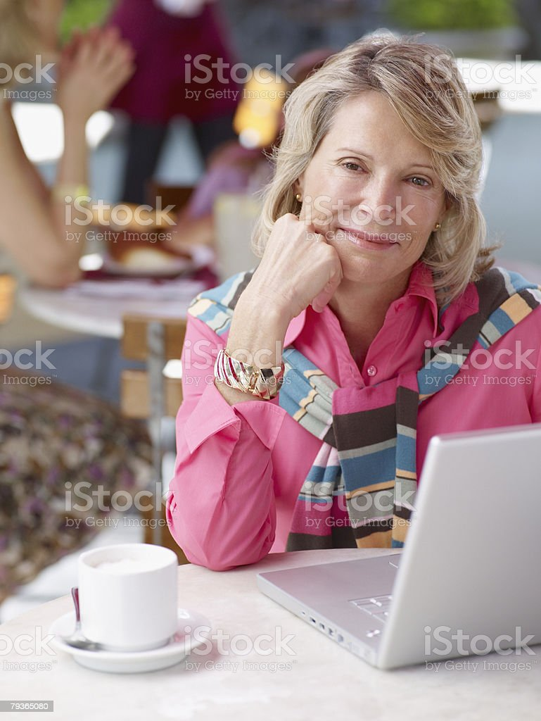 Woman on outdoor patio with laptop royalty-free stock photo