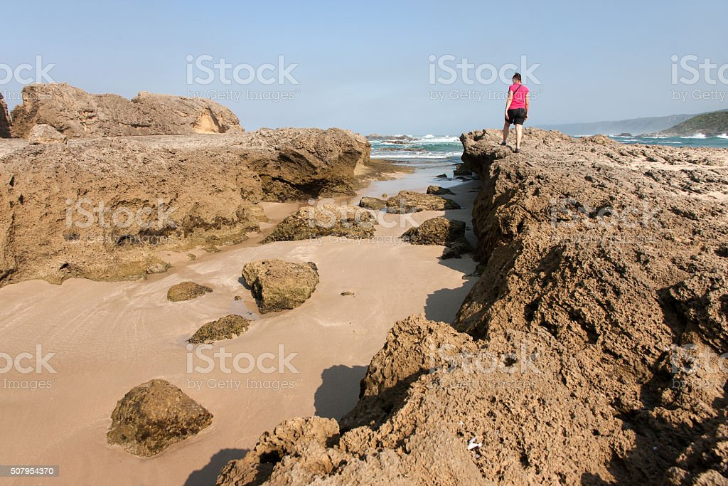 Woman on petrified dunes at Eersterivier Beach South Africa 1 stock photo