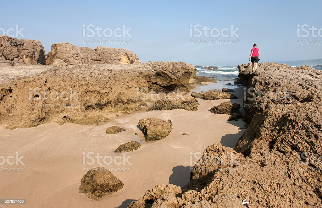 Woman on petrified dunes at Eersterivier Beach South Africa 2 stock photo