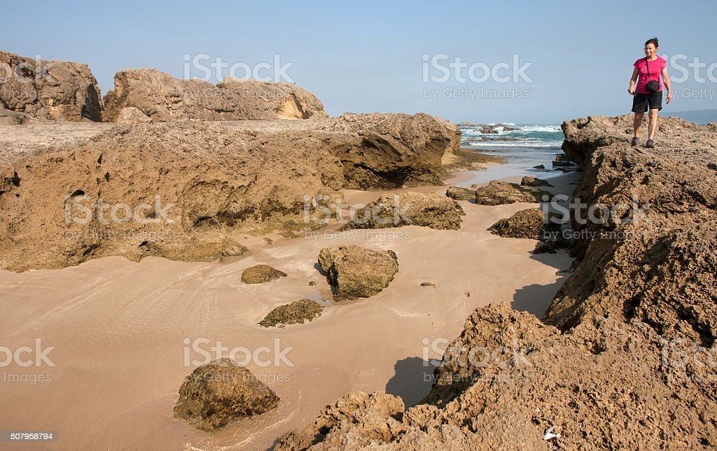 Woman on petrified dunes at Eersterivier Beach South Africa 3 stock photo