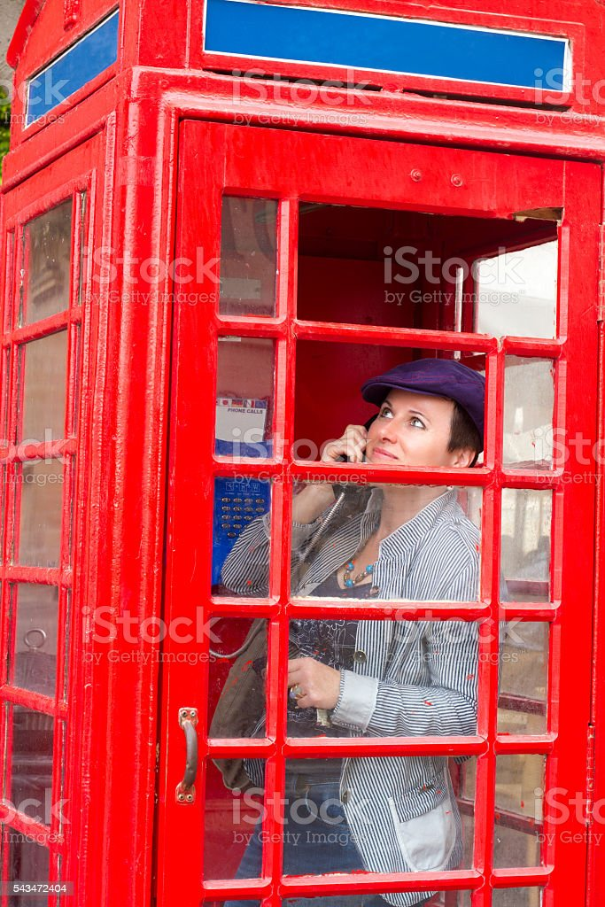 Woman on Phone in Vintage British Red Telephone Box stock photo