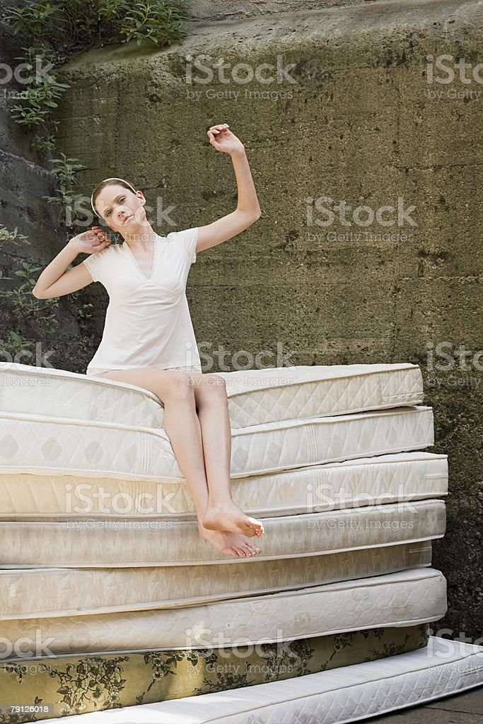 Woman on pile of mattresses stock photo