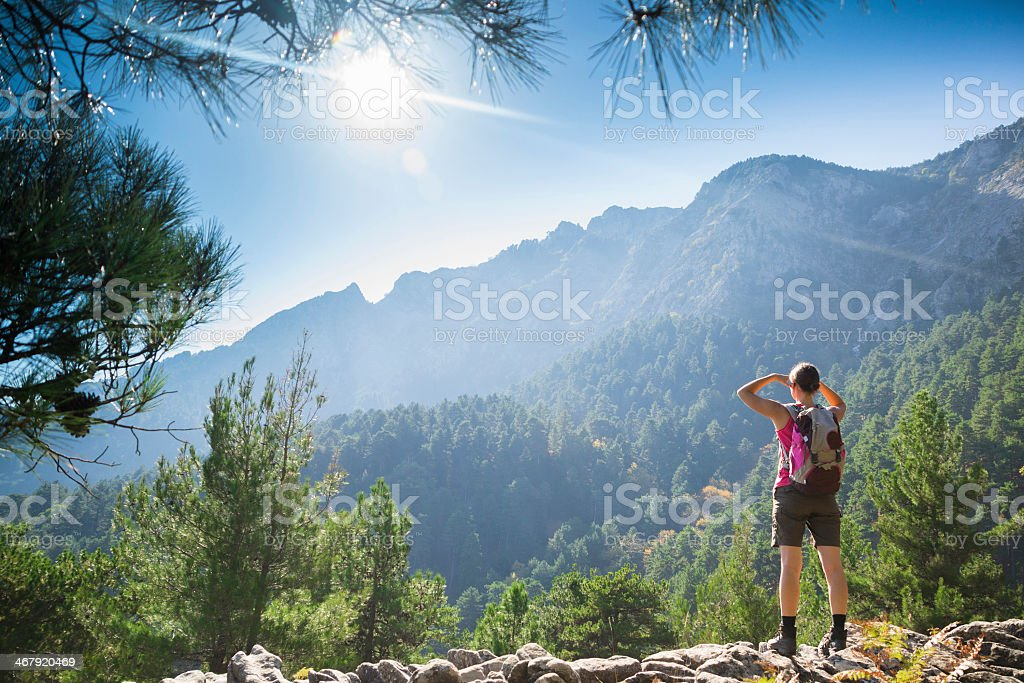Woman on rocks and looking out to the mountains after hiking stock photo