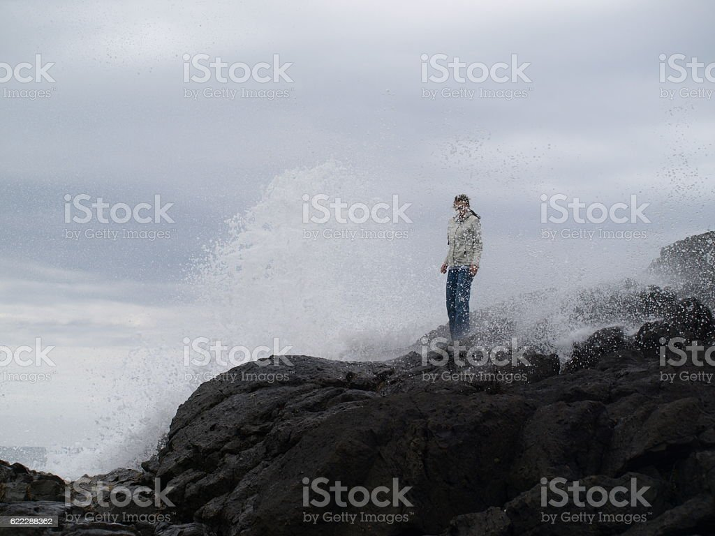 Woman on rocks being splashed by large ocean wave stock photo