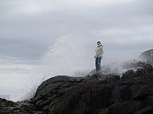 Woman on rocks being splashed by large ocean wave
